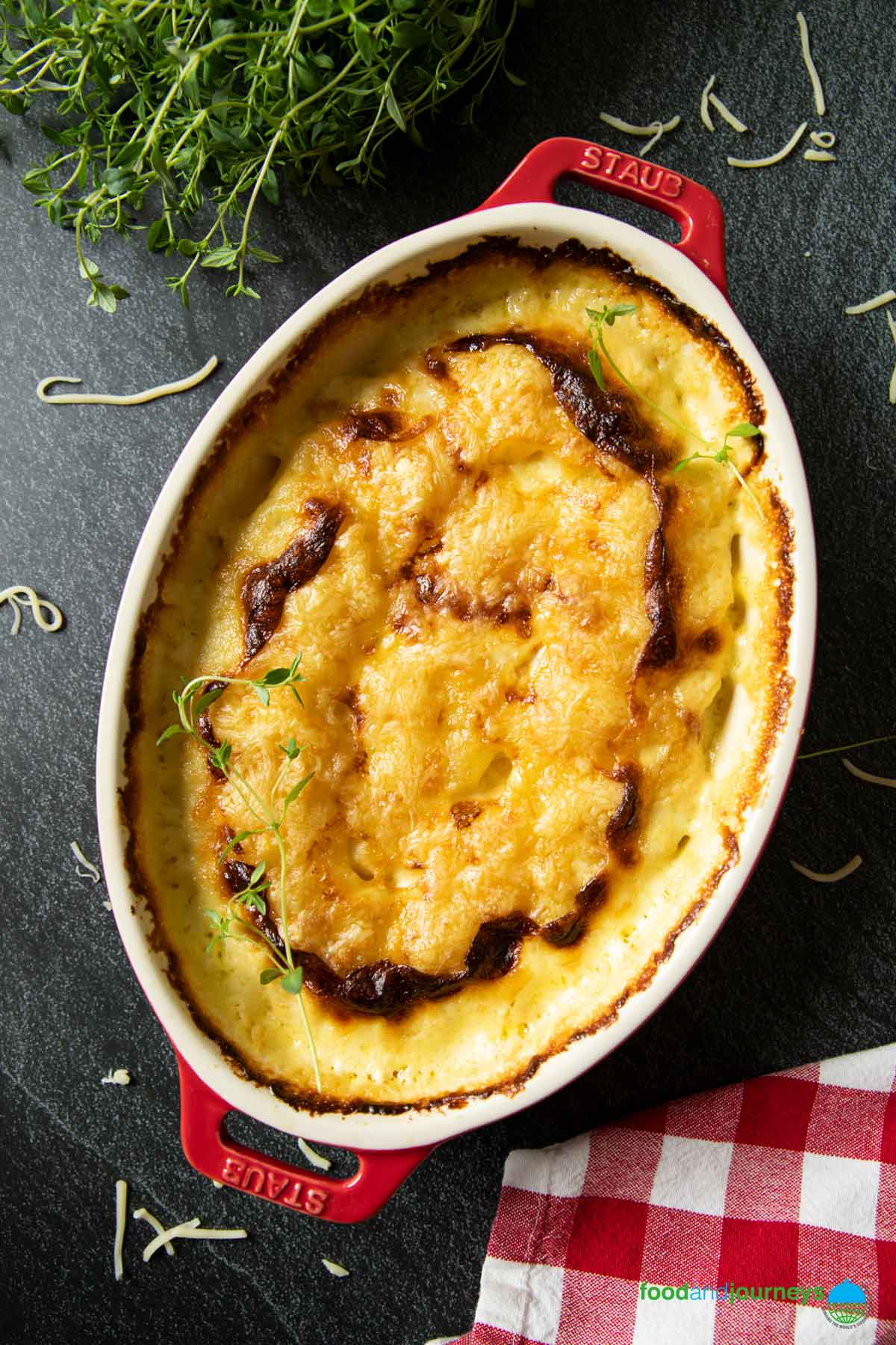 An overhead shot of German Potato Gratin, fresh out of the oven, with some fresh thyme on the background.
