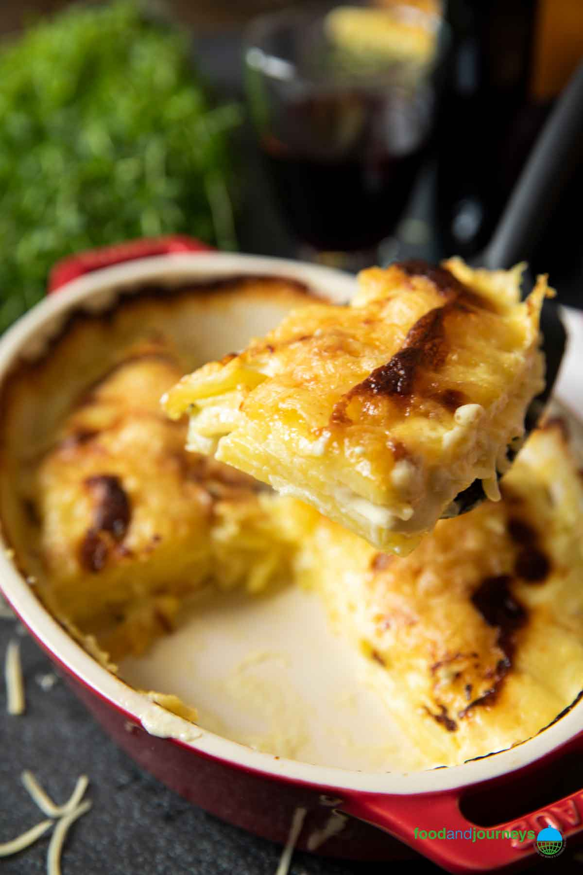 A shot of a serving of German potato gratin, about to be placed on a plate.