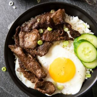 An overhead shot of a bowl of tapsilog, with dipping sauce and a cup of coffee on the side.