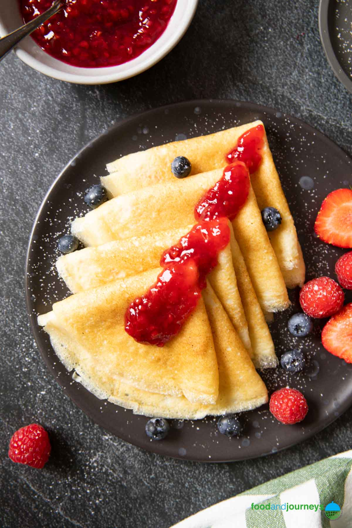 An overhead shot of thin pancakes folded into quarters, with raspberry jam on top.