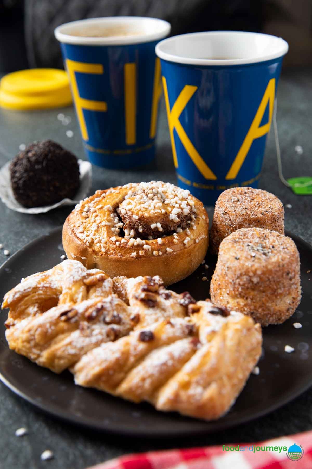 A plate of mixed Swedish treats, served with coffee and tea; for a typical Swedish fika.