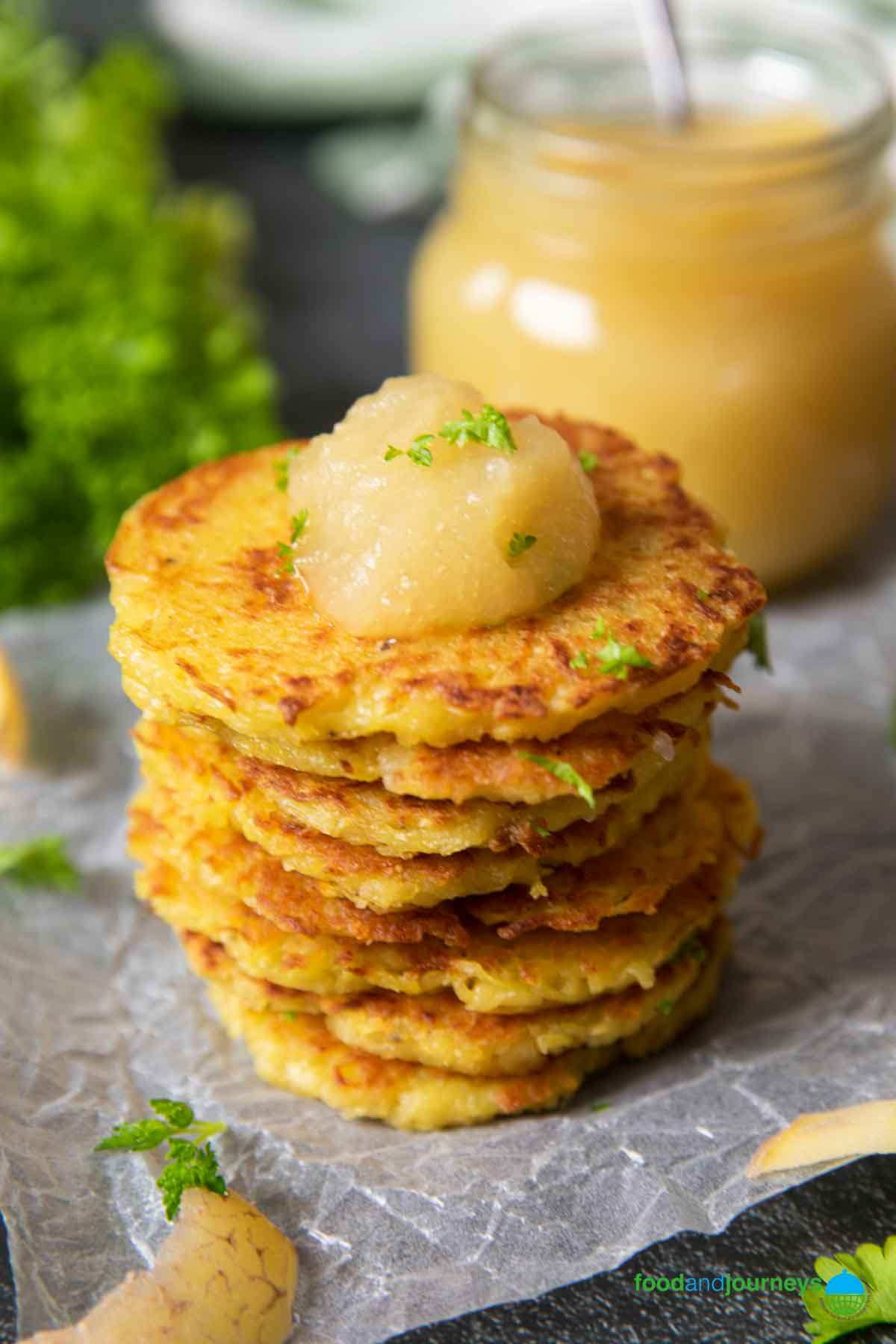 A stack of potato pancakes, with a jar of applesauce on the background, and a dollop on top.