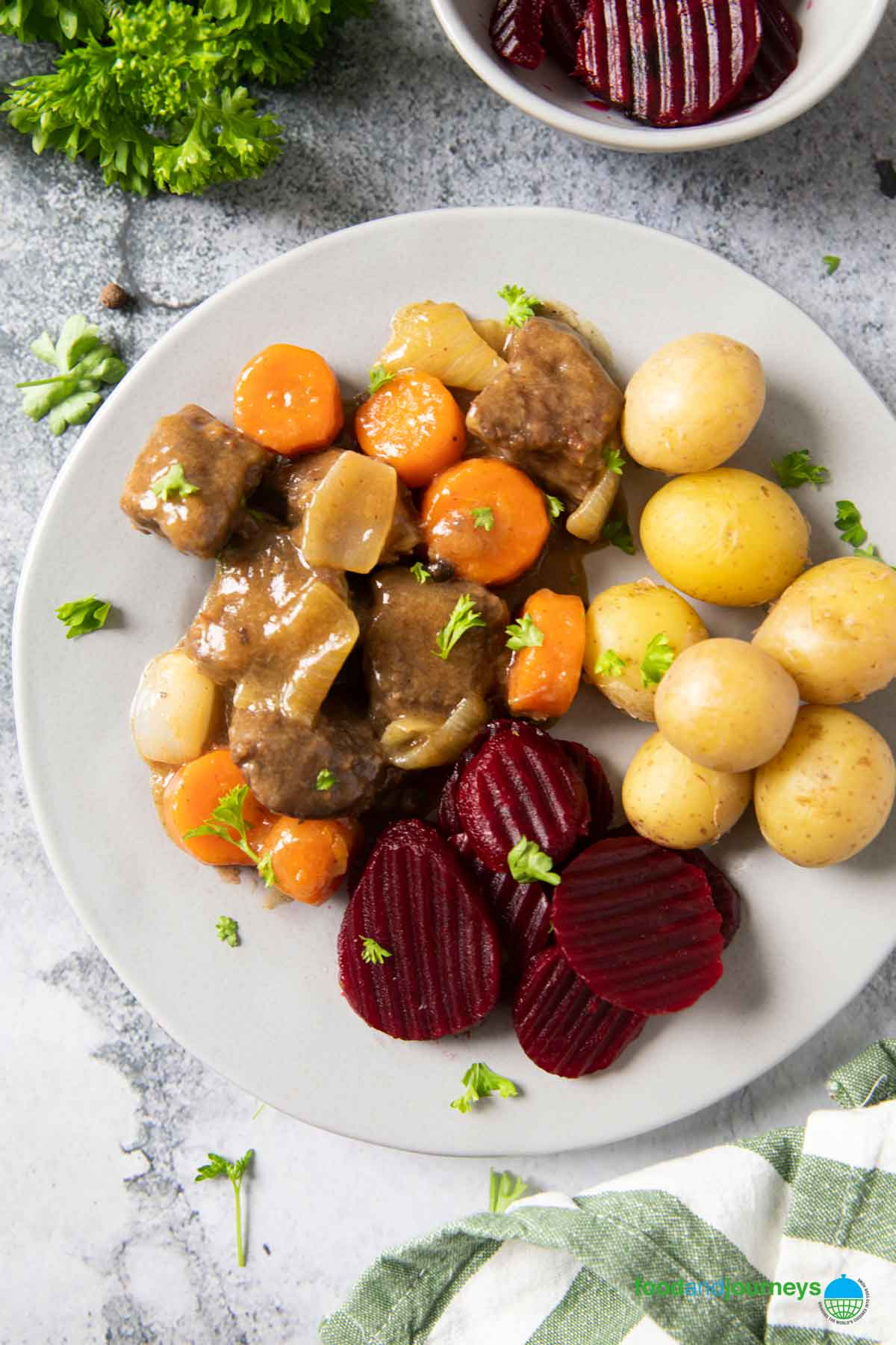 An overhead shot of how beef stew with allspice is served in Swede, with boiled potatoes and pickled beets.