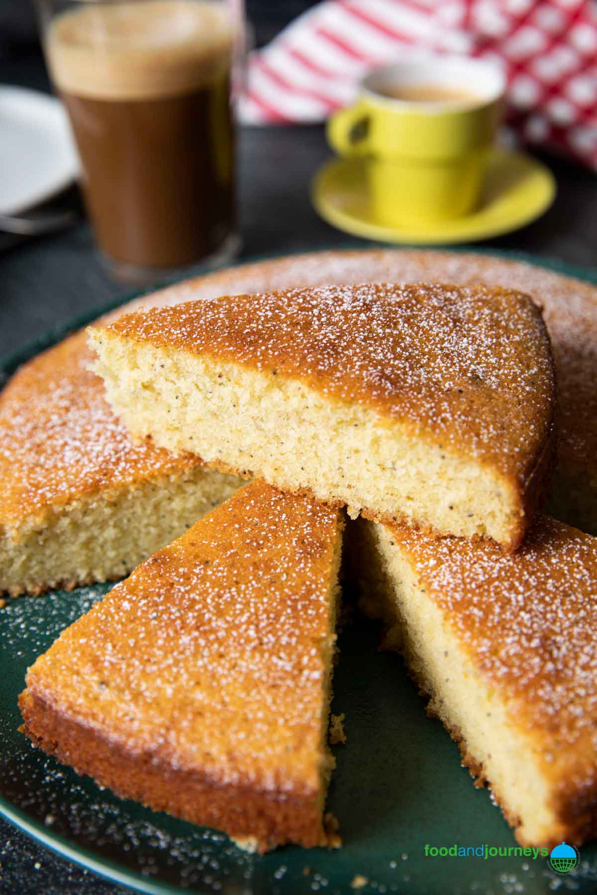 A closer shot of a slice of cardamom cake, showing the bits of ground cardamom in the cake, and its buttery texture.