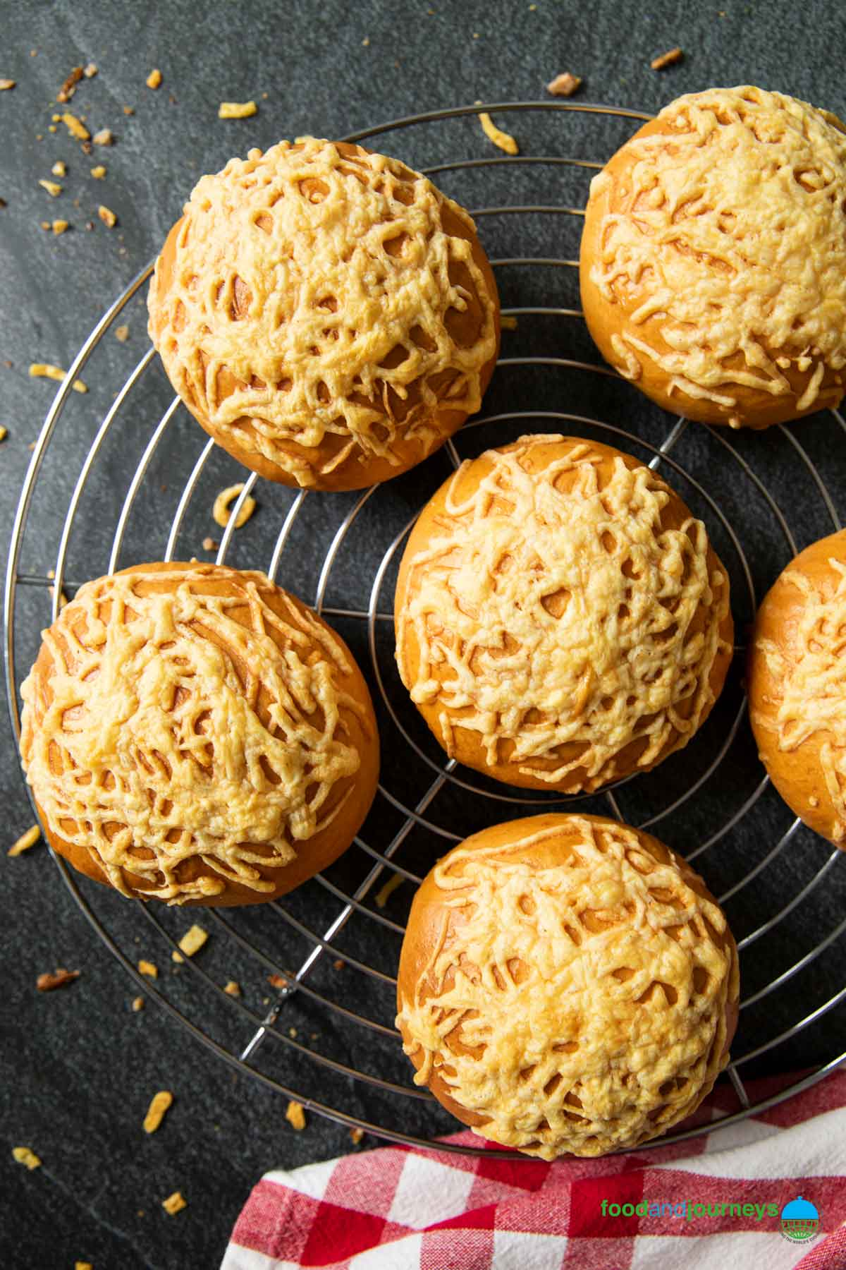 An overhead shot of freshly baked Swedish cheese buns on a cooling rack.