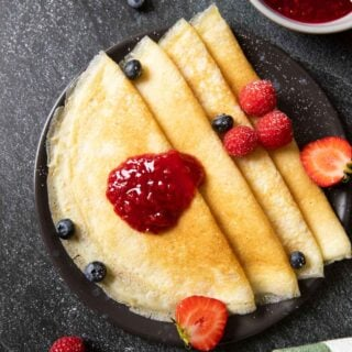 An overhead shot of a plate of Swedish pancakes, served with raspberry jam and fresh fruits.