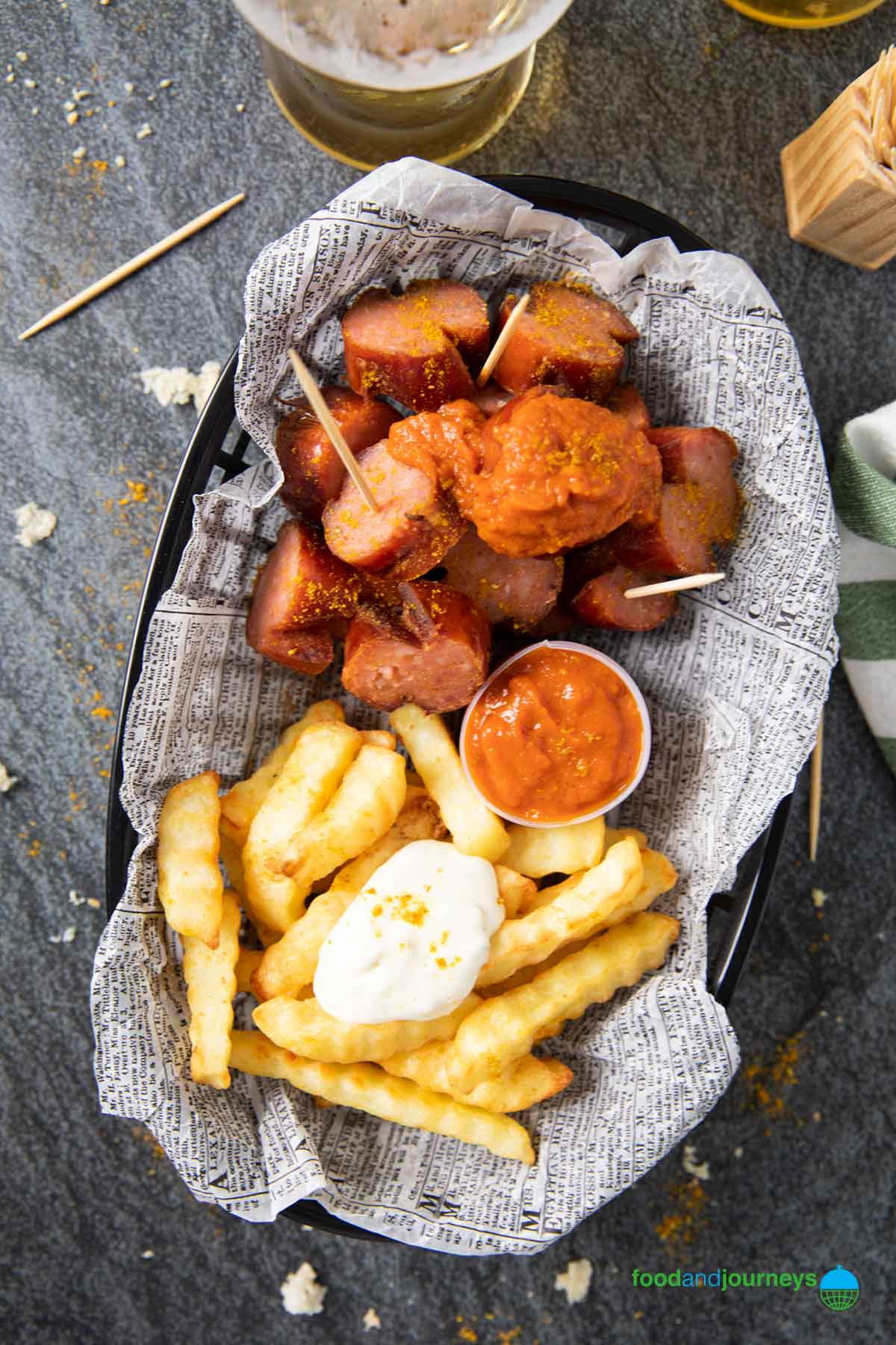 Overhead shot of a serving of currywurst, with a glass of beer on the side.