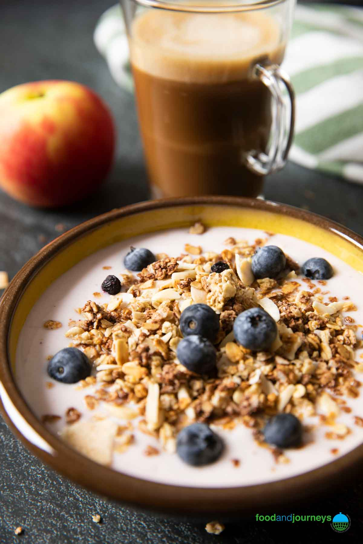 A bowl of muesli and light yogurt, with a mug of coffee and an apple in the background.