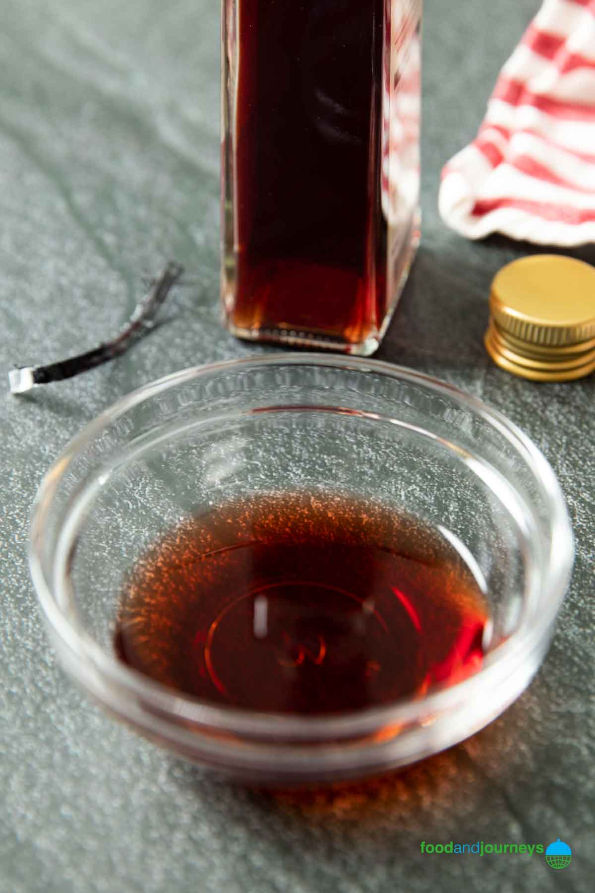 Red winee vinegar poured into a small bowl, with a bottle of it in the background.
