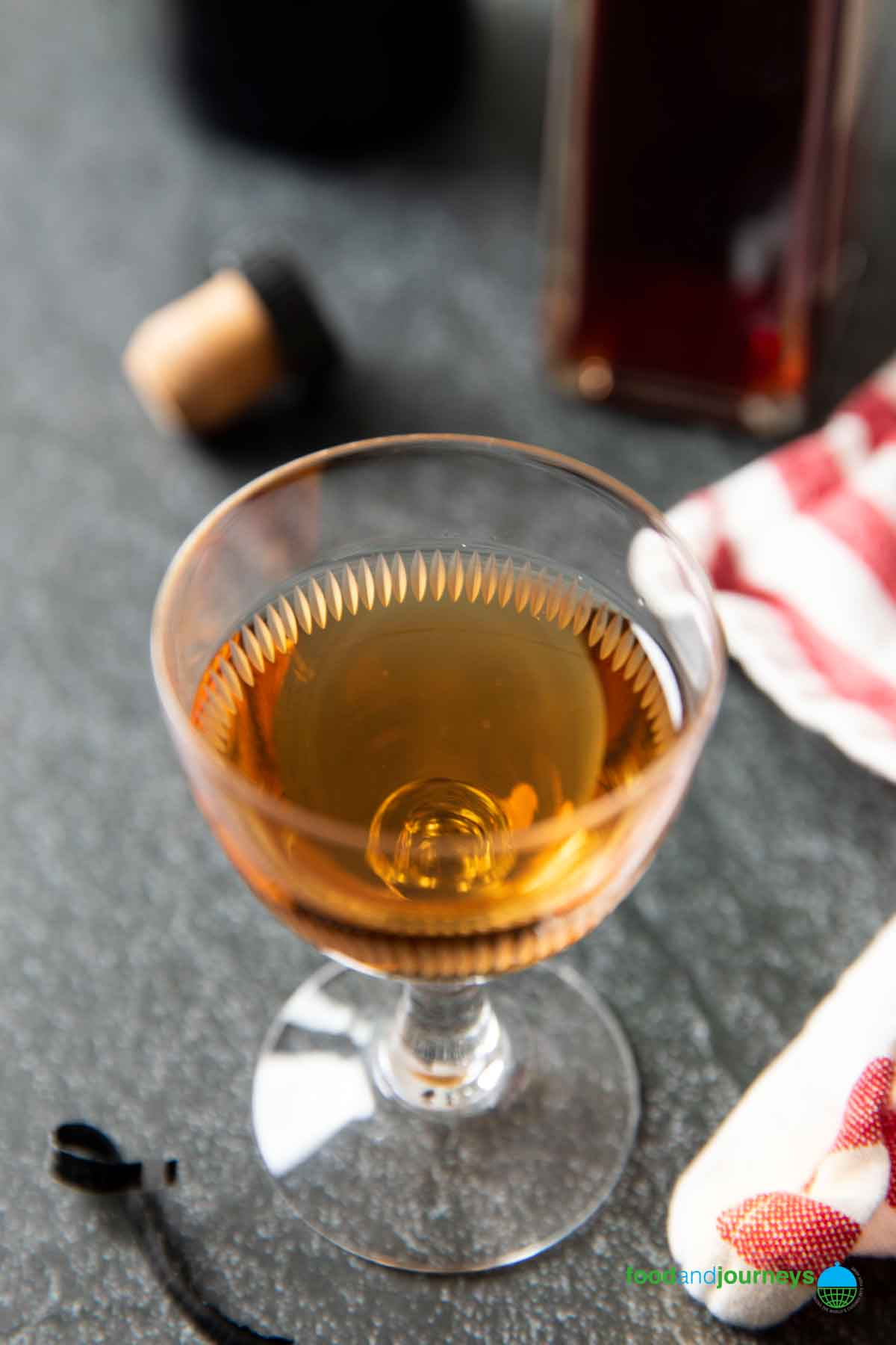 Sherry wine poured into a small glass, with a bottlee of red wine vinegar in the background.