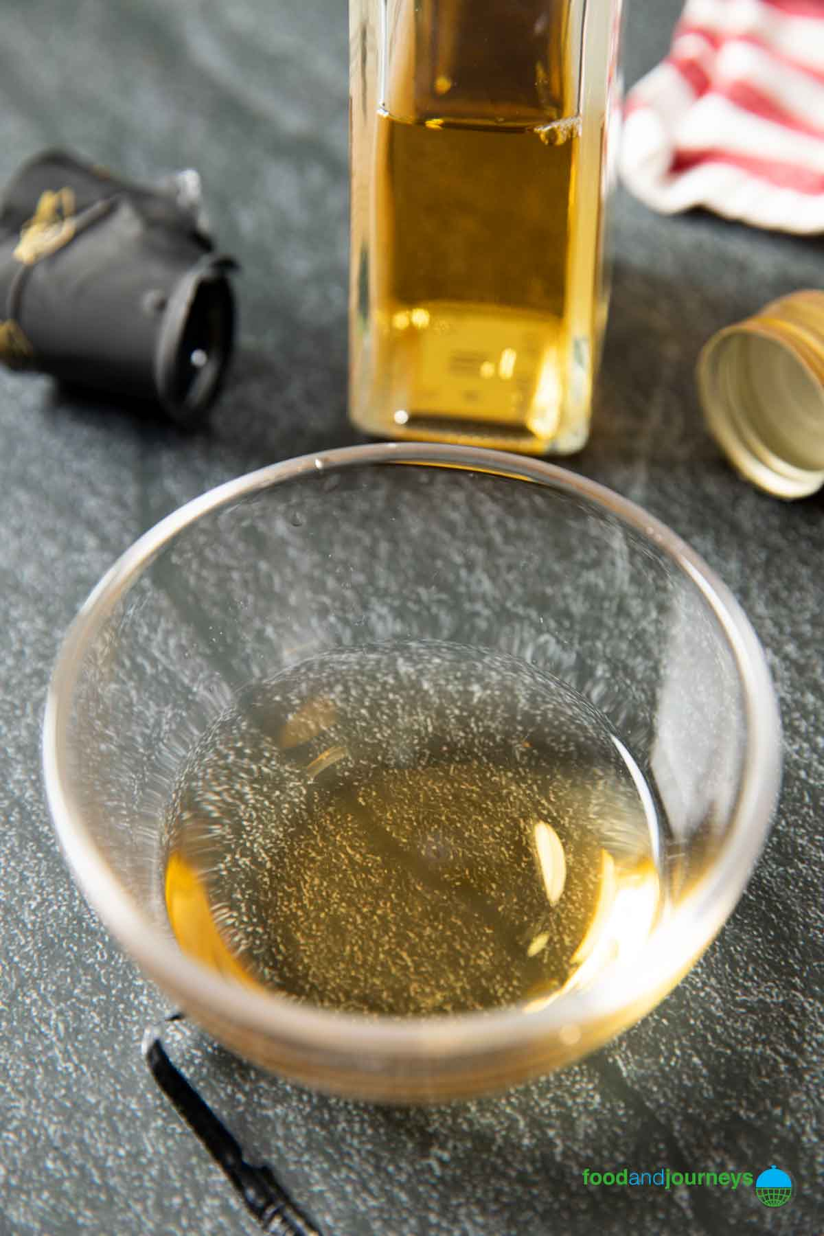 White wine vinegar poured into a small bowl, with a bottle of it in the background.